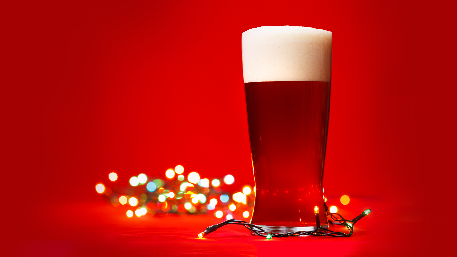 a glass of beer with christmas lights in the background