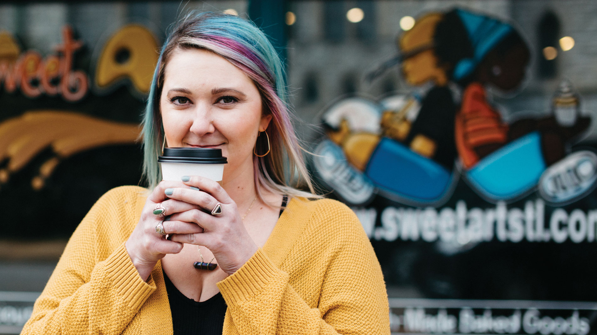 a woman with multicolored hair and a yellow sweater holding a cup of coffee outside sweetart bakery