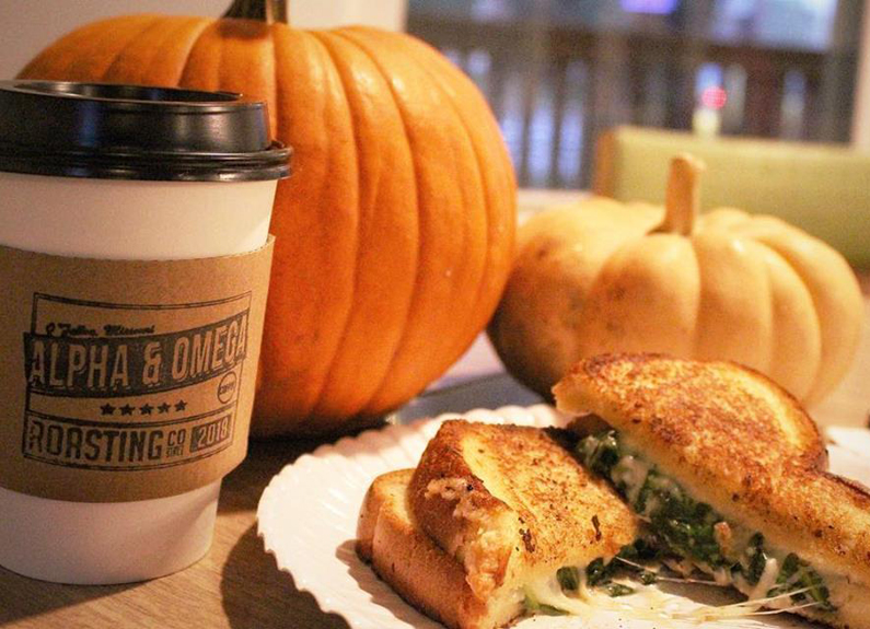 a paper coffee cup and a grilled cheese sandwich