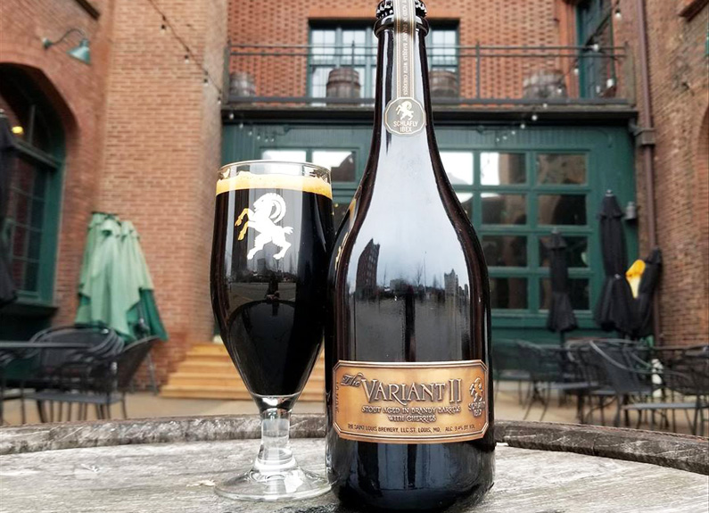 a large bottle of beer next to a glass of dark beer on a patio