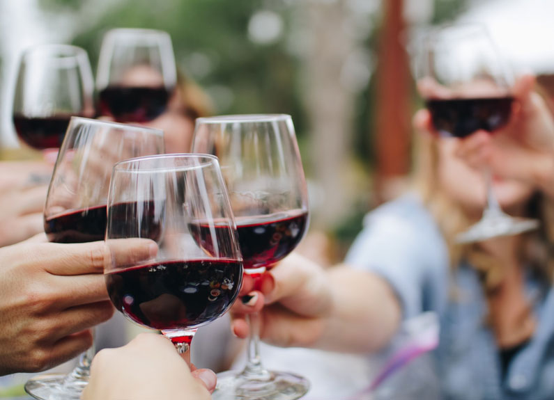 several hands toasting with red wine glasses