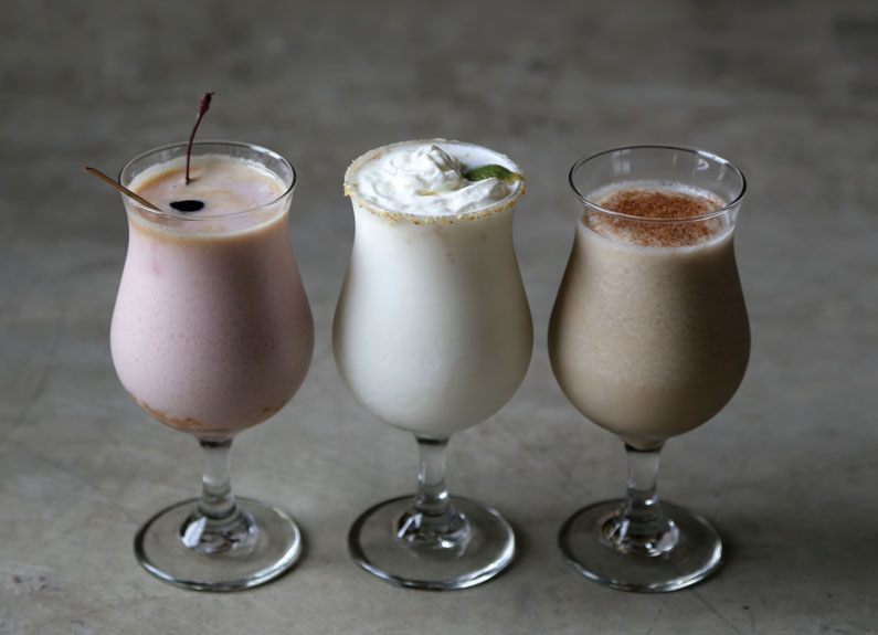 three tulip glasses filled with blended frozen drinks