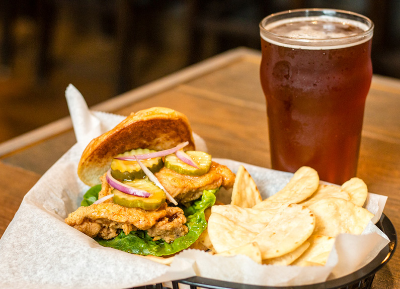 spicy chicken thigh sandwich with pita chips and beer at twisted roots brewing co. in st. louis
