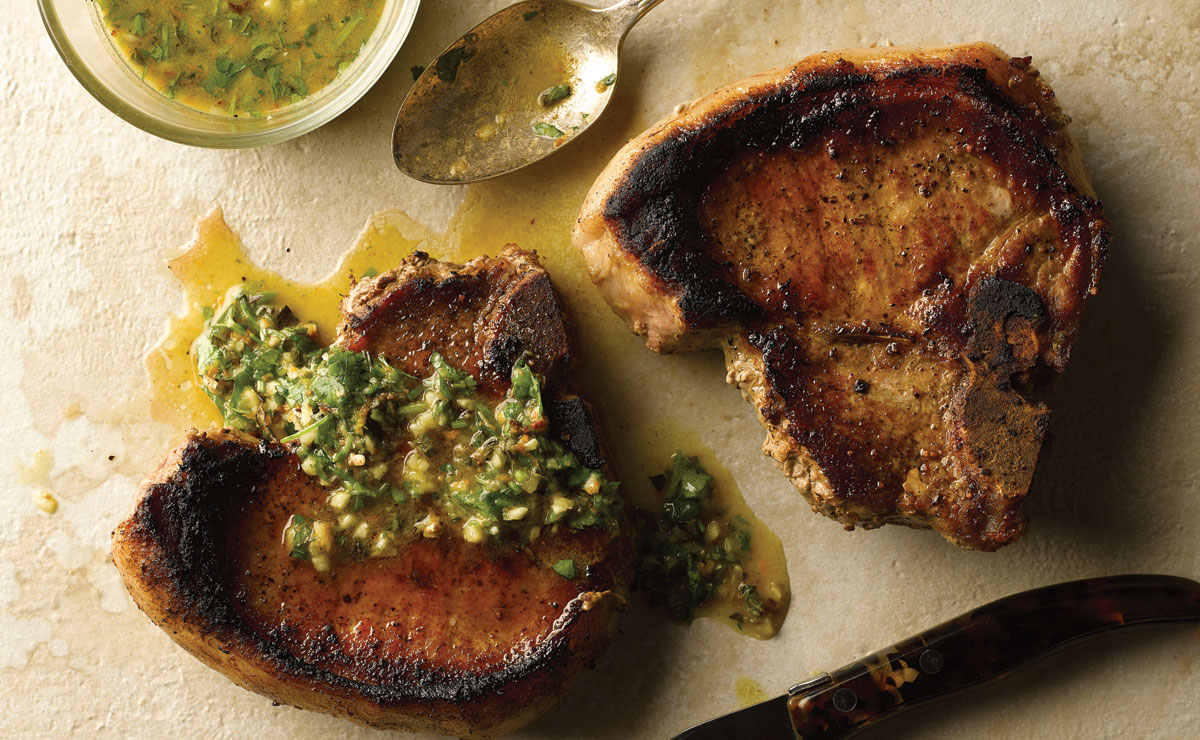 two pork chops covered in mojo sauce