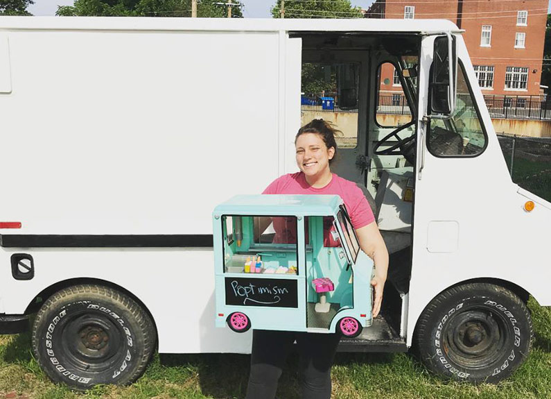 whisk owner kaylen wissinger holding a mini food truck in front of a larger truck
