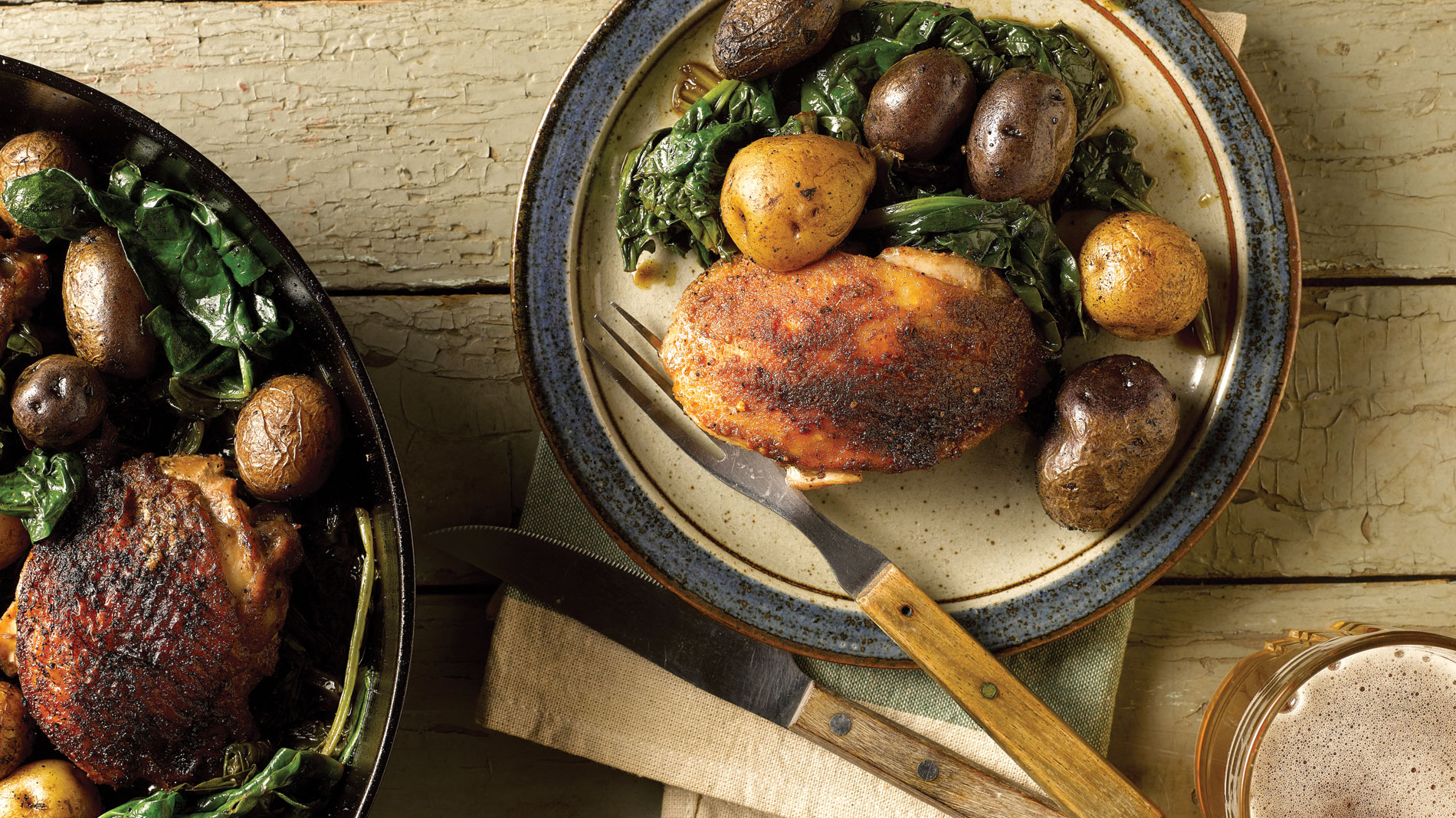 skillet with chicken thigh, potatoes and spinach