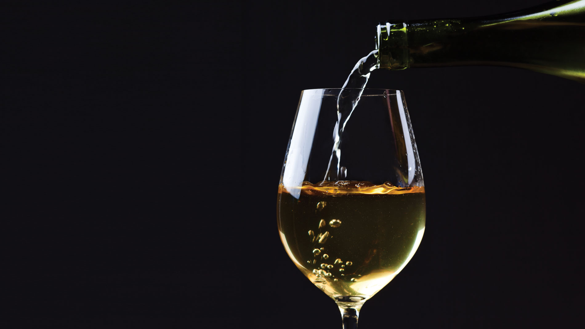 white wine pouring into a glass