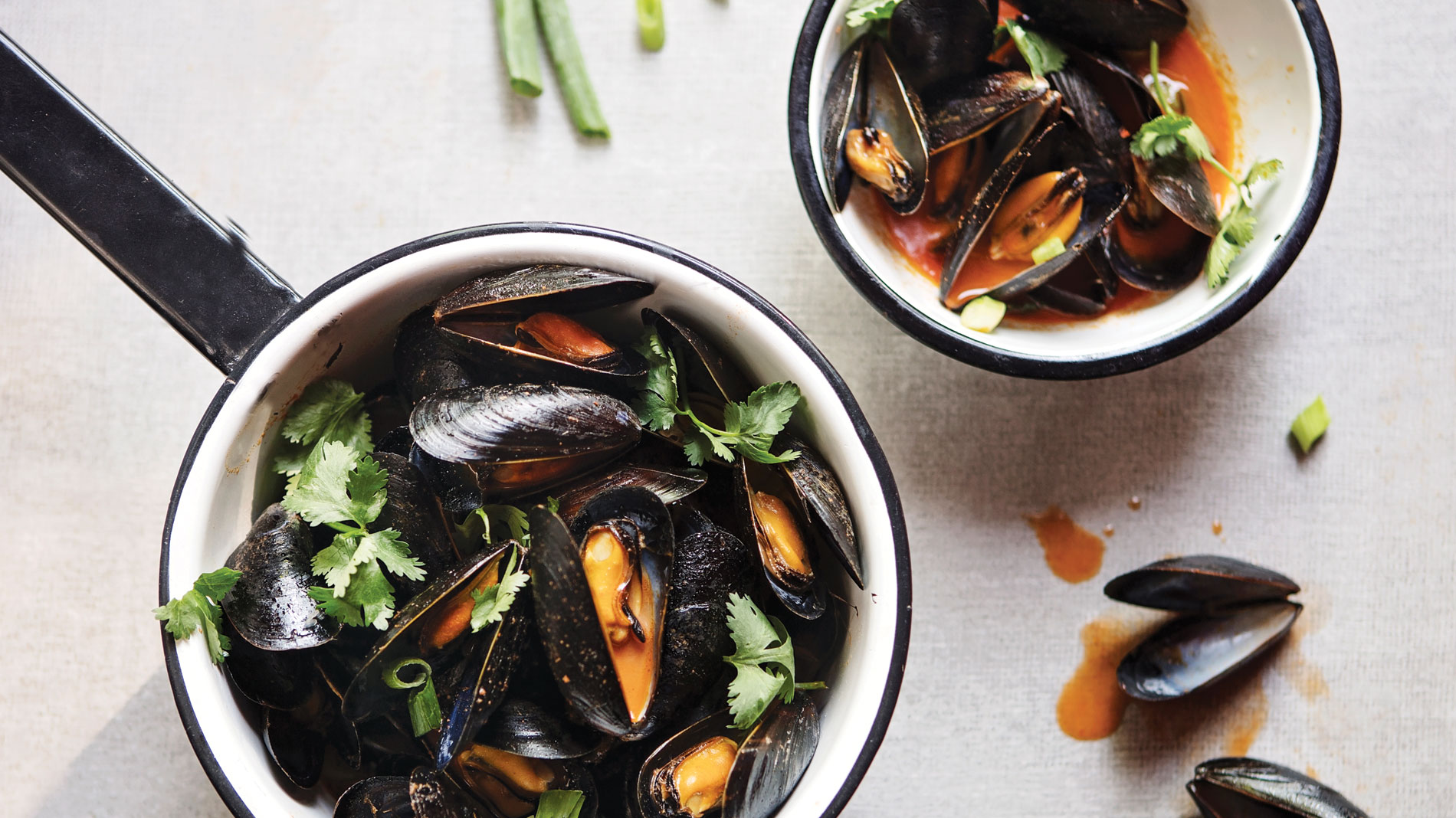 grilled mussels with red curry in a cast-iron skillet