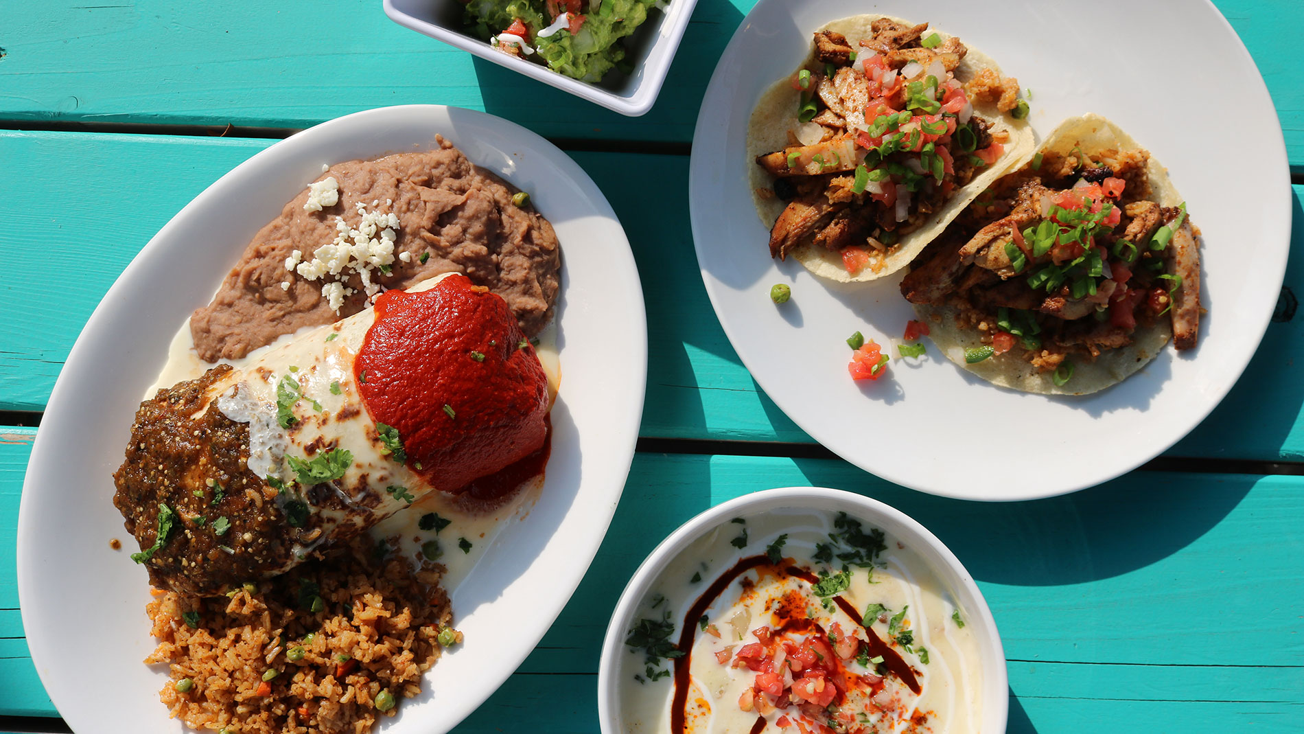 four dishes of mexican food on a blue table