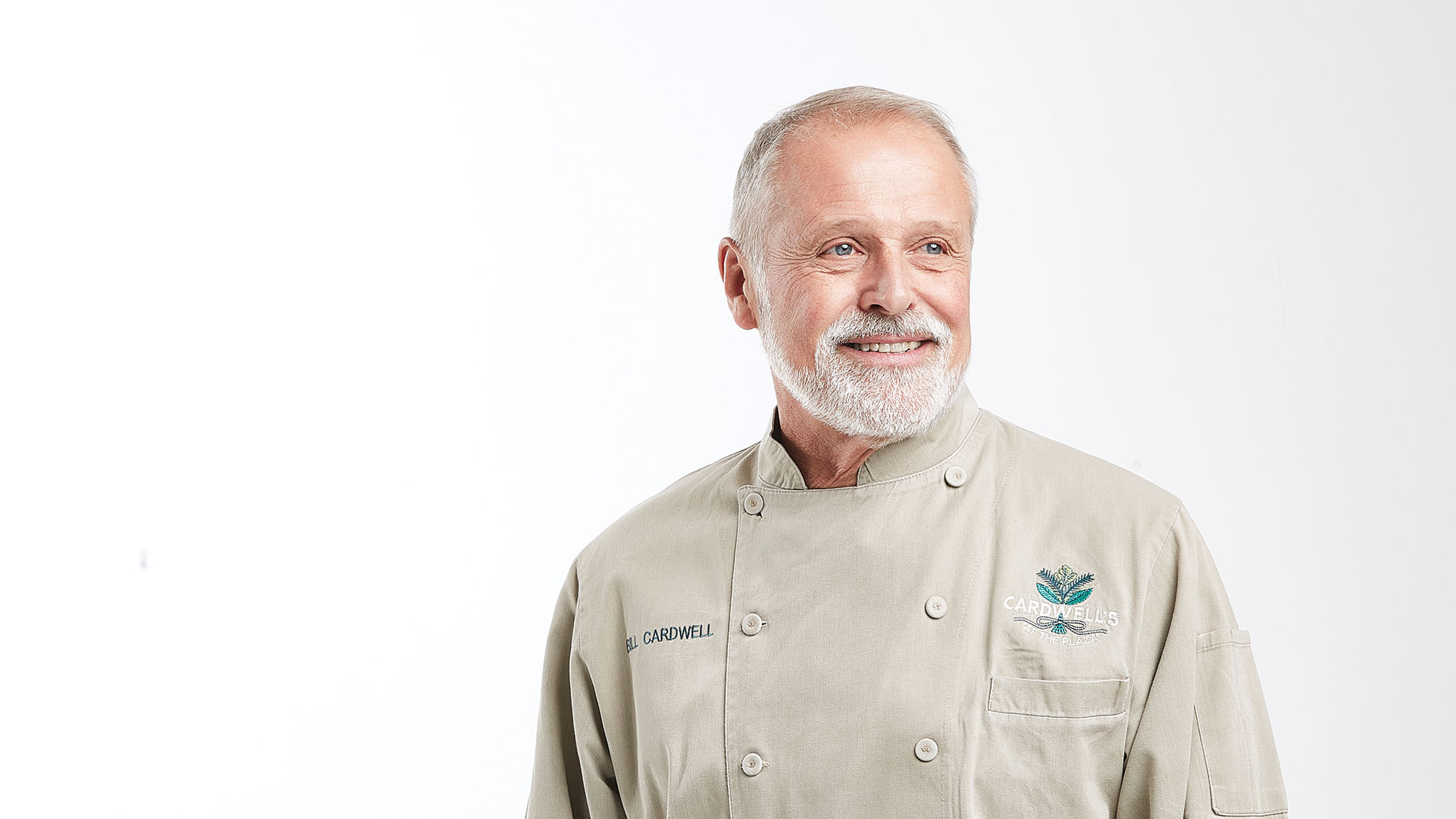 a man with a gray beard and a chef coat