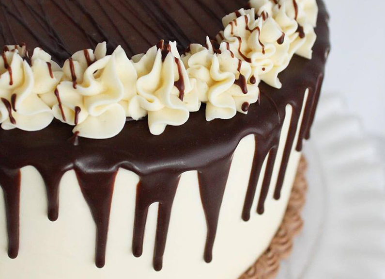 a white cake with chocolate icing dripping over the edge