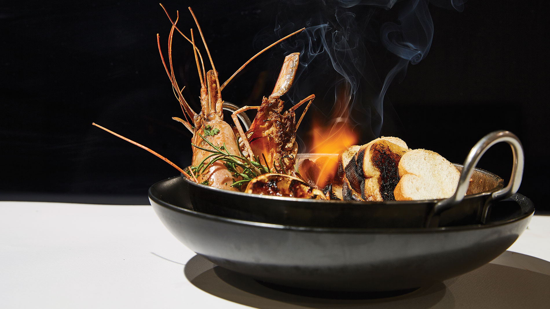 prawn cooking in a flame-filled black bowl