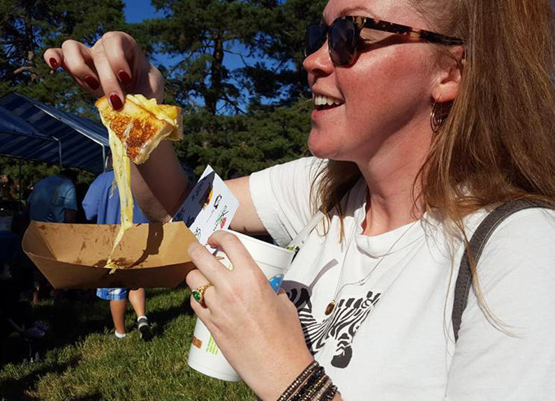a woman with sunglasses eating a grilled cheese