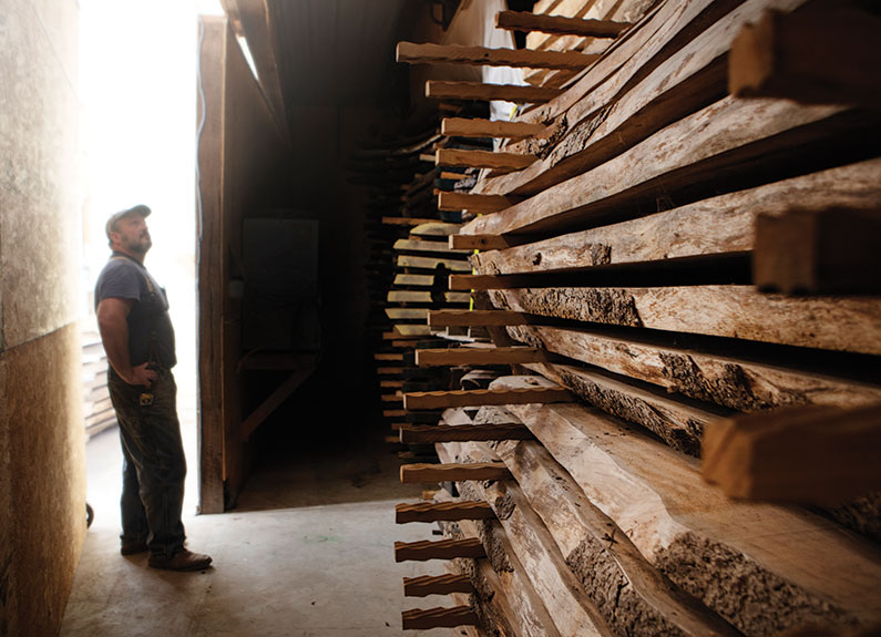 a man looking at slabs of wood in a barn
