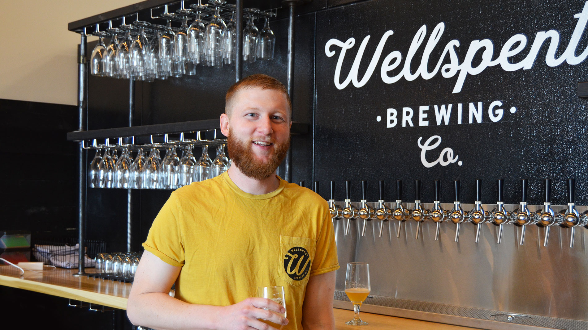 a smiling man behind a bar with a glass of beer