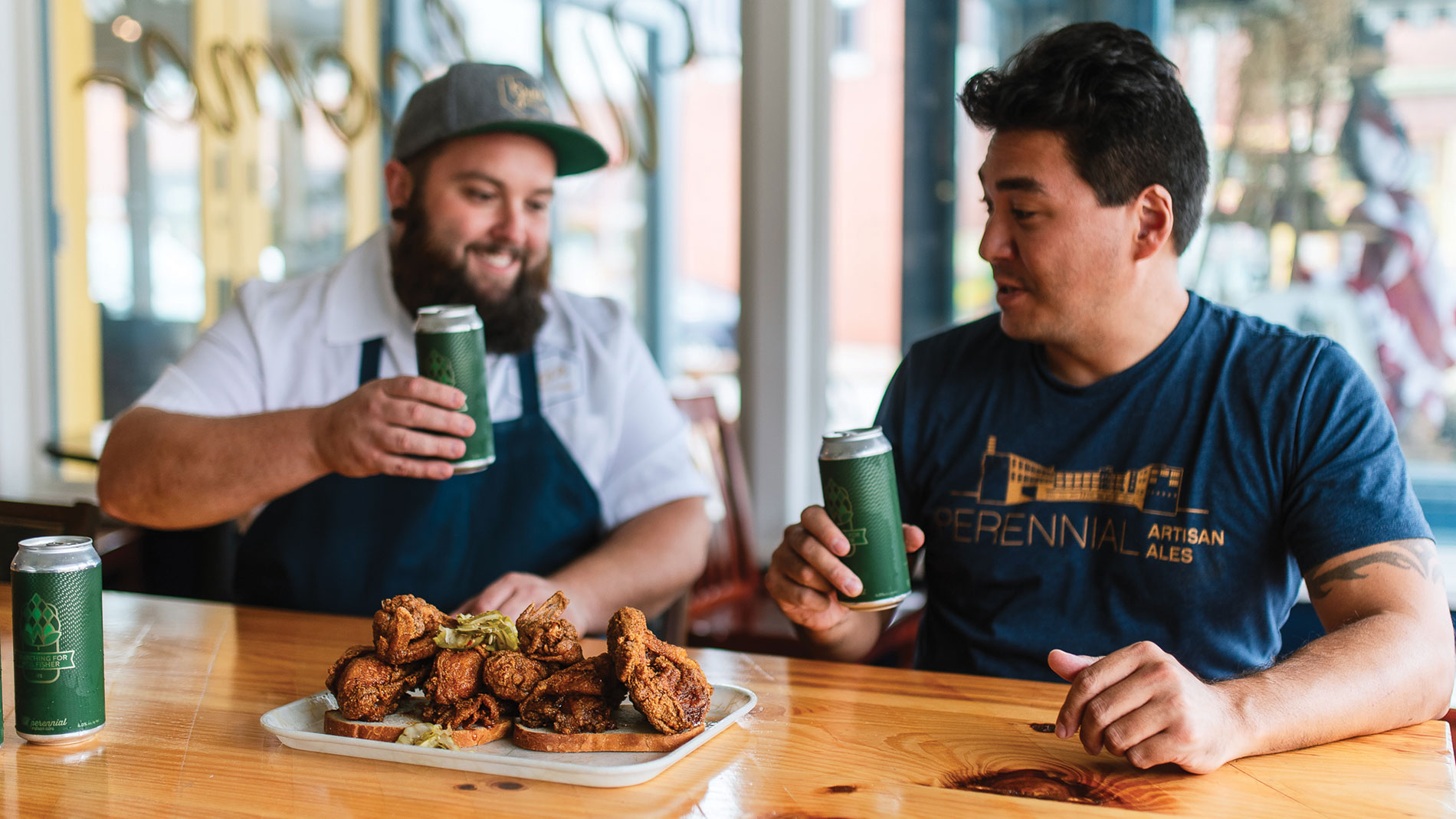 two men drinking beer with a plate of fried chicken