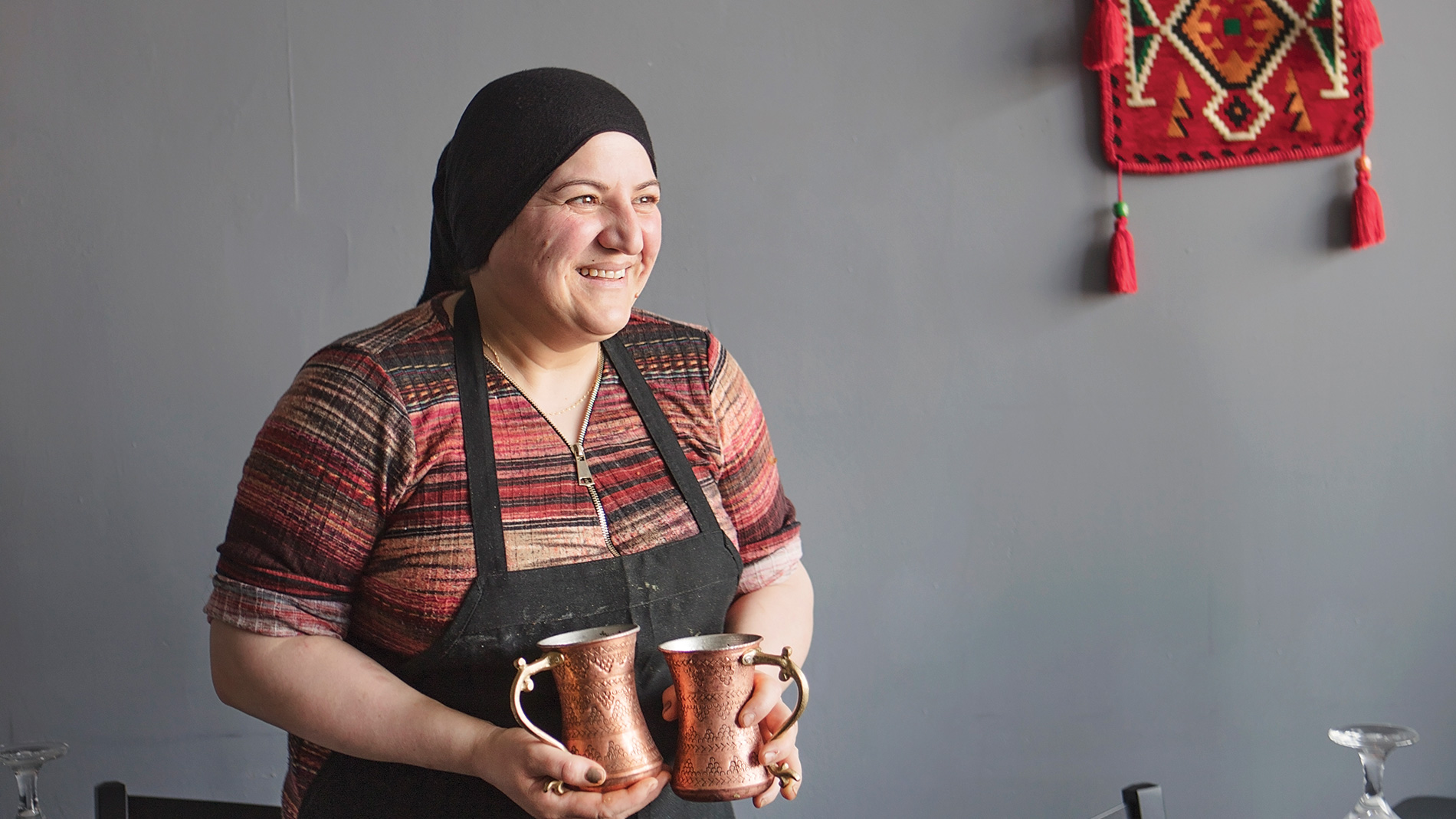 a woman in a black apron holding copper pitchers