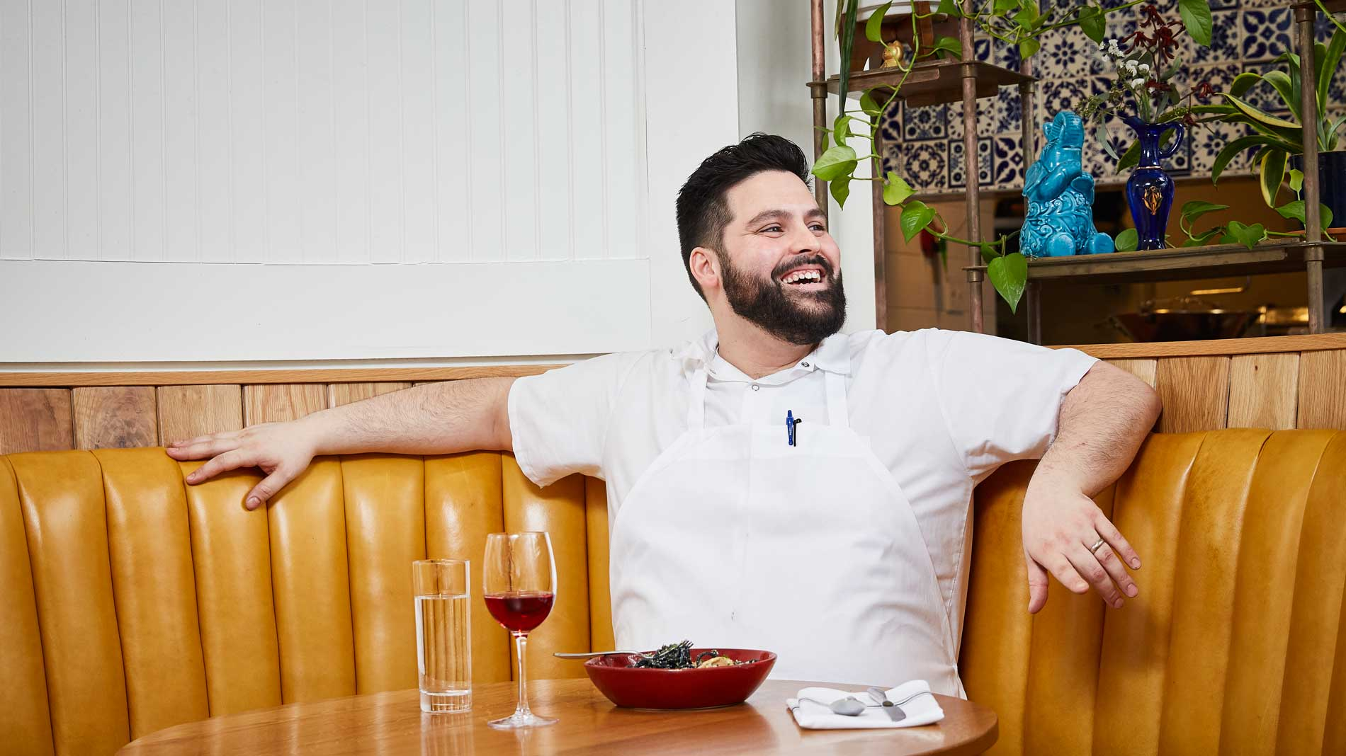 a bearded chef sitting at a yellow restaurant banquette