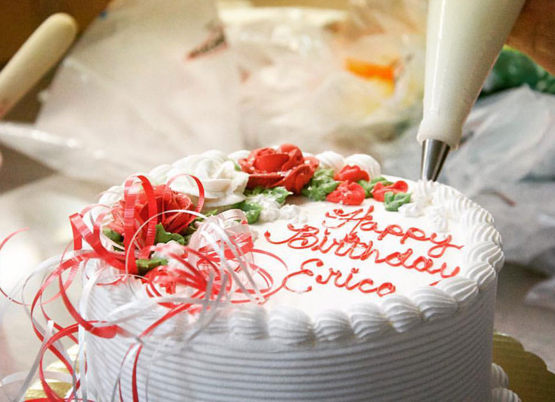 a round birthday cake with white icing and red lettering