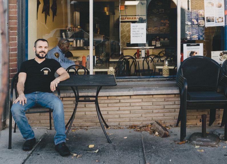 a smiling man sitting outside shawarma king restuarnat