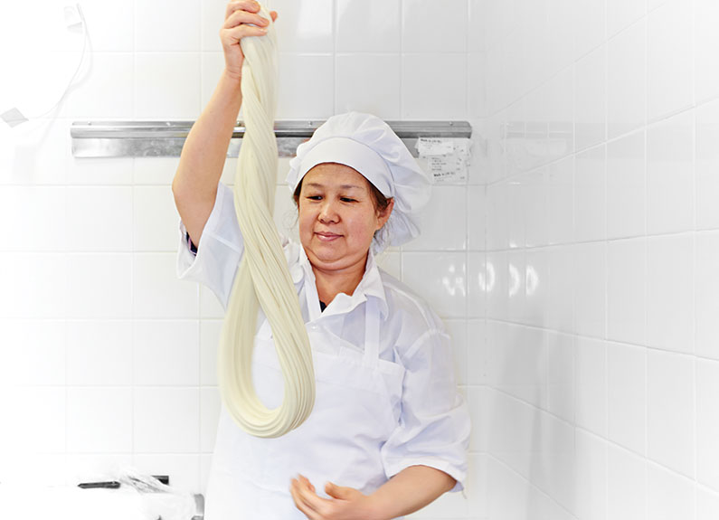 Chef Wang pulling dough into noodles at corner 17 in the loop