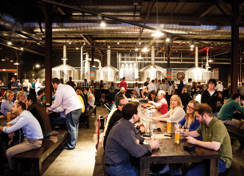 many people sitting at long wooden tables in a cavernous beer hall