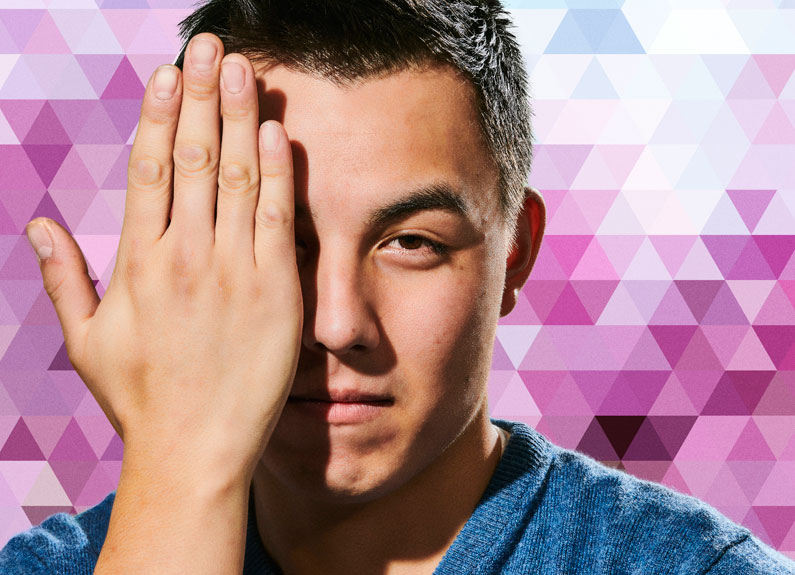 a young man holding his hand in front of half of his face against a patterned background
