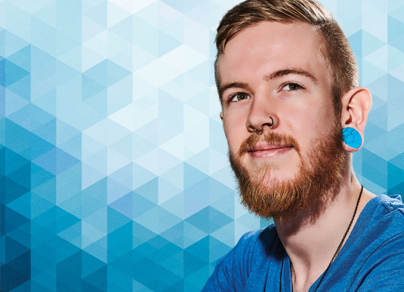a young man with a beard, nose rings and ear gauges against a blue ombre background