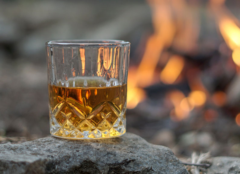 a glass of whiskey on top of a barrell