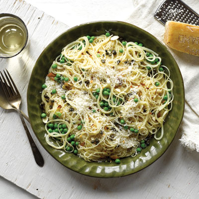 a large plate filled with spaghetti and peas topped with parmesan