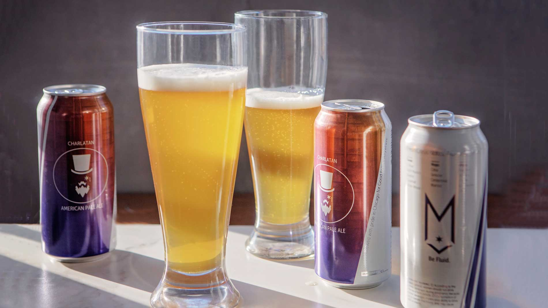 Three cans of beer with two pilsner glasses filled with beer