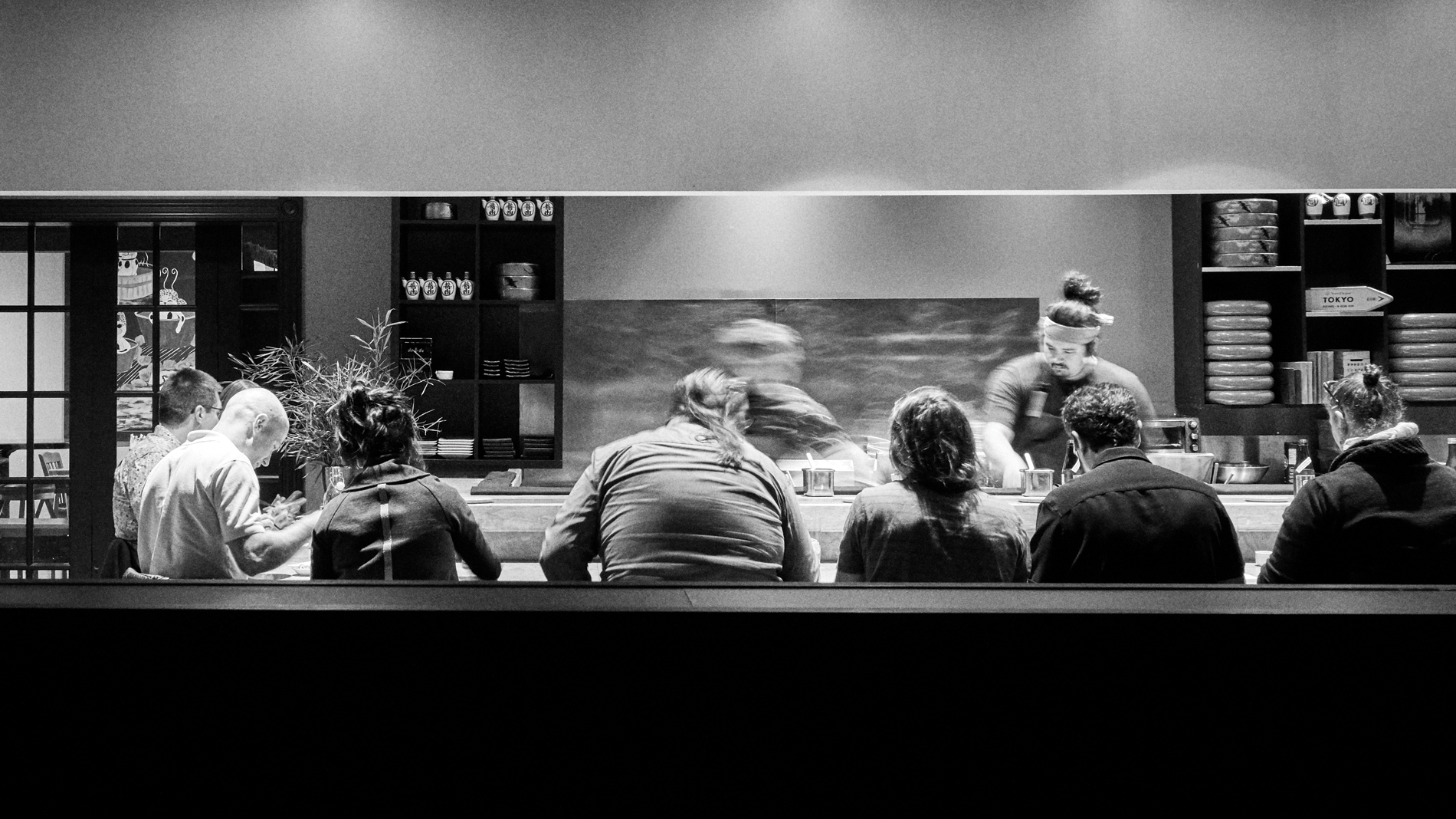 a black and white image of a sushi chef working at a crowded bar