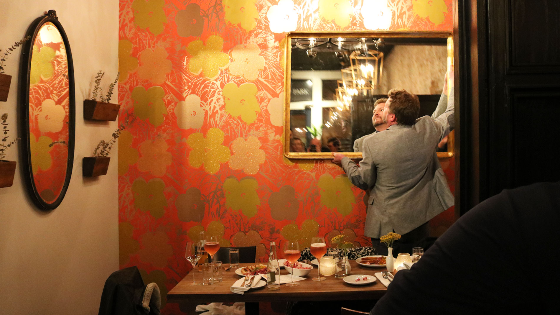 a man adjusting a large gilt mirror in a restaurant