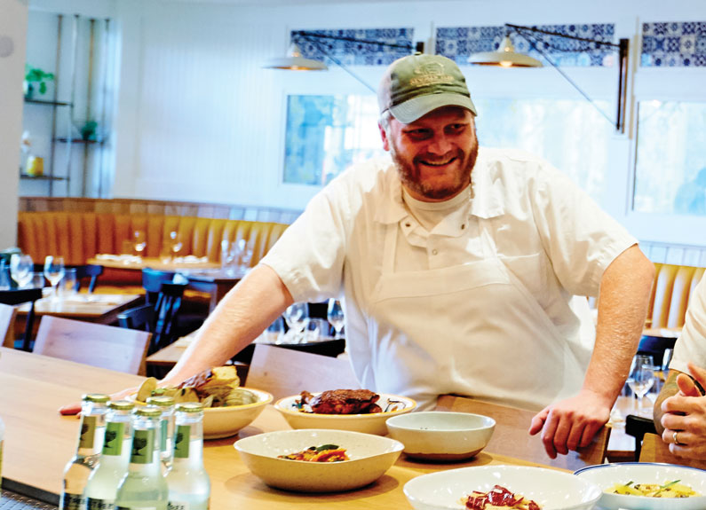 a smiling chef in a green baseball hat and white apron leaning against a bar with dishes