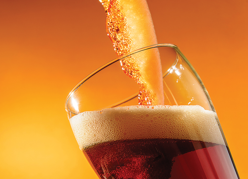 a beer being poured into a glass on a yellow background