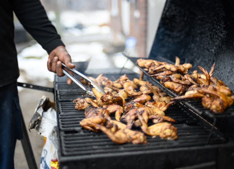 a man's hand holding a pair of silver tongs and flipping several jerk chicken wings on a black grill