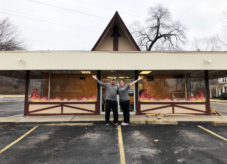 a couple posing with arms in the air outside a barbecue restaurant