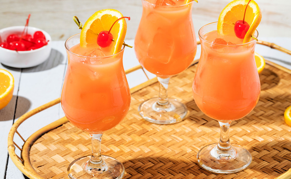 three hurricane cocktails on a straw tray
