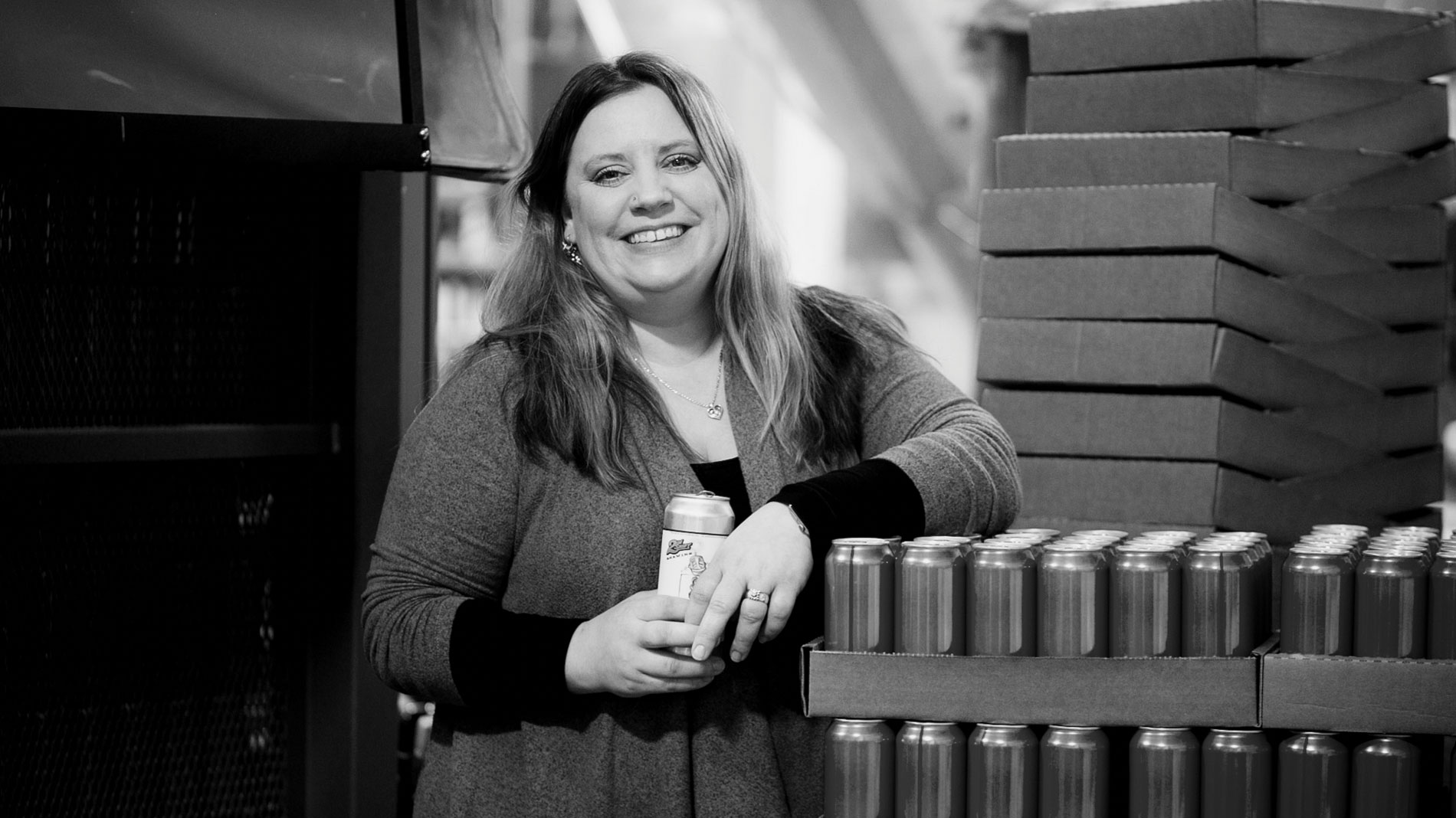 a smiling woman holding a can of beer and leaning against pallets of beer