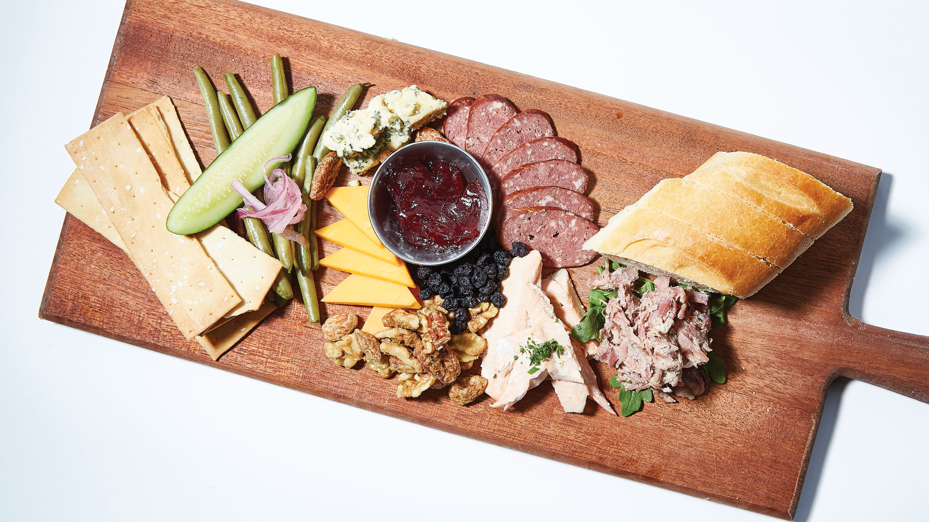 a large wooden plank filled with meats and cheese