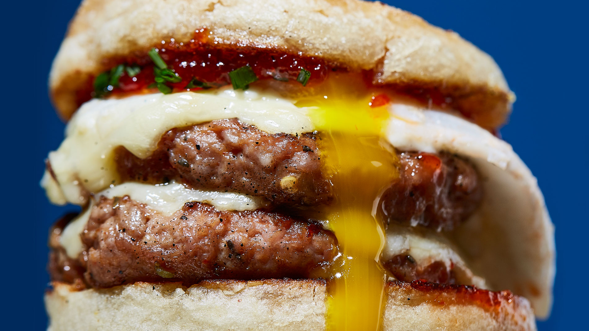 a close-up photo of double sausage patty breakfast sandwich with cheese and egg