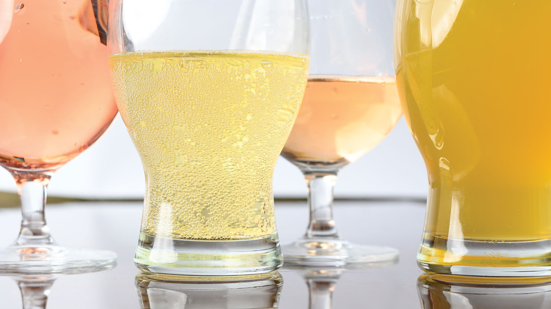 close up shot of several rose colored glasses of cider