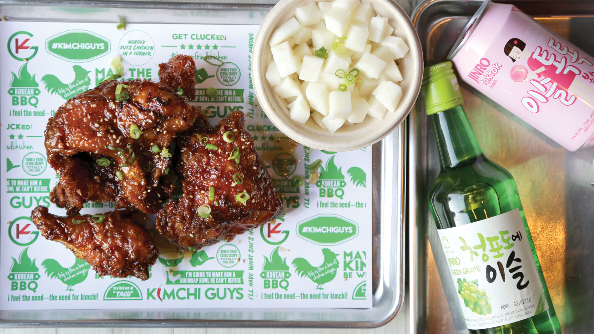 A tray with Korean fried chicken, white radish kimchi and bottles of Jinro soju