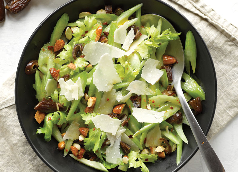 a bowl of celery salad with almonds and parmesan cheese