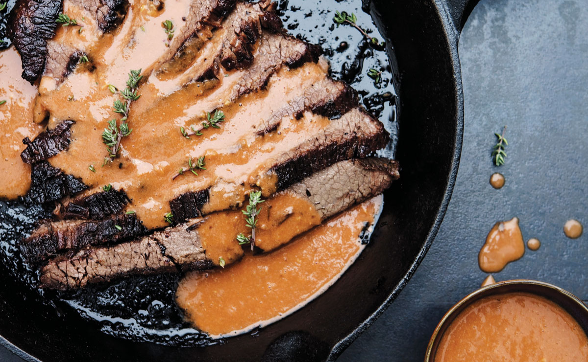 A cast iron pan with sliced brisket and a sauce made of tomatoes and garlic