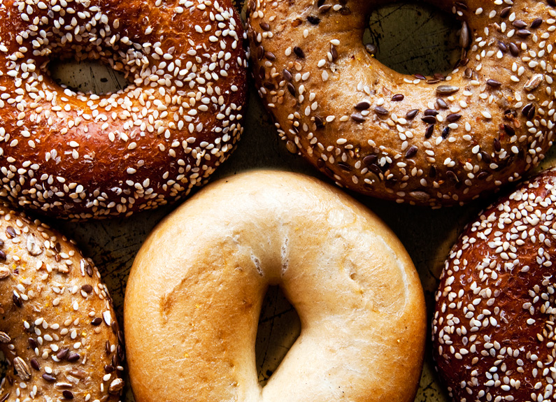 a close up photo of several poppy seed, sesame seed and plain bagels