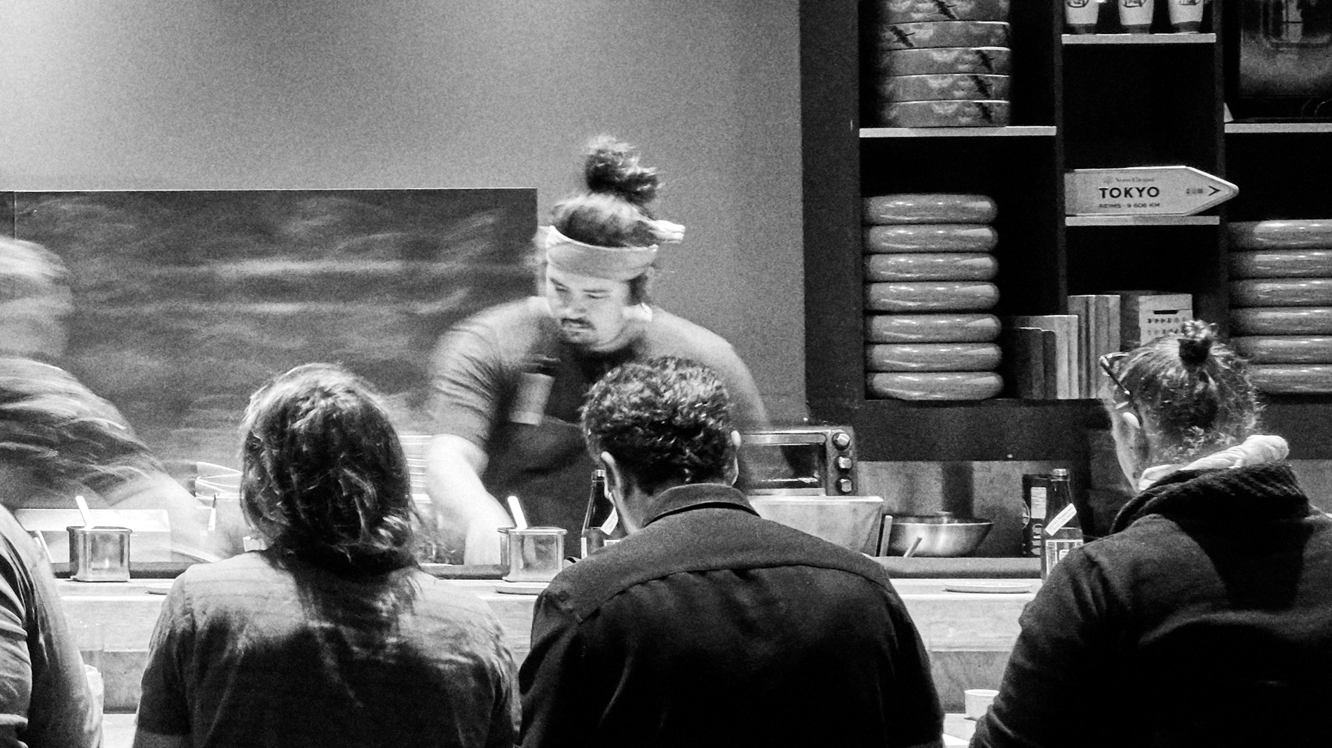 a sushi chef in action at a busy sushi bar