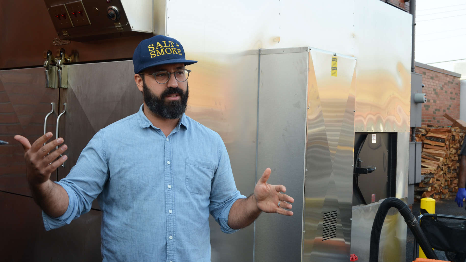 a bearded man in a baseball cap standing next to a barbecue smoker
