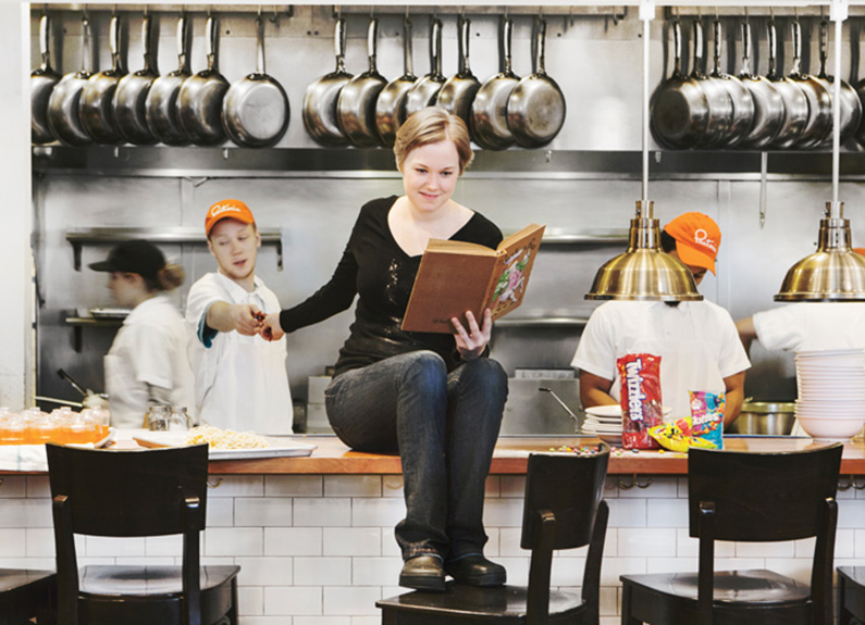 a young woman sitting on a bar reading a book and handing candy to a cook