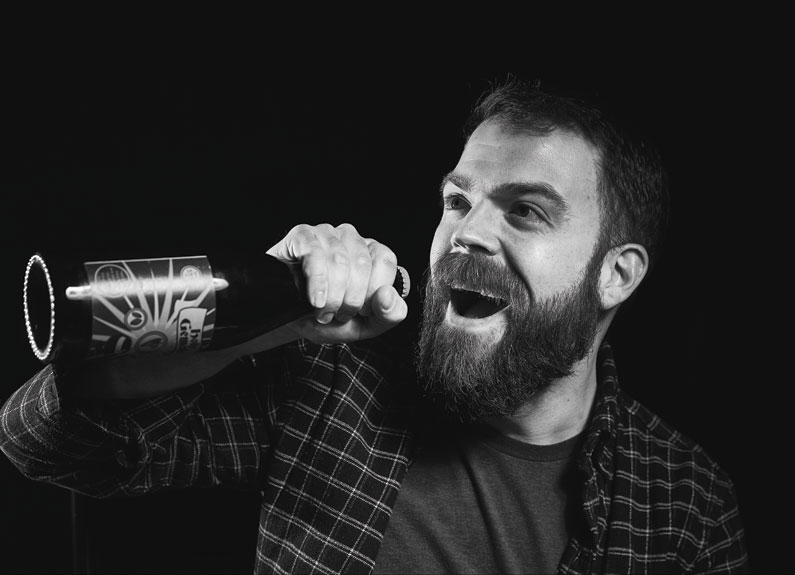 a black and white photo of a bearded man holding a large bottle of heer